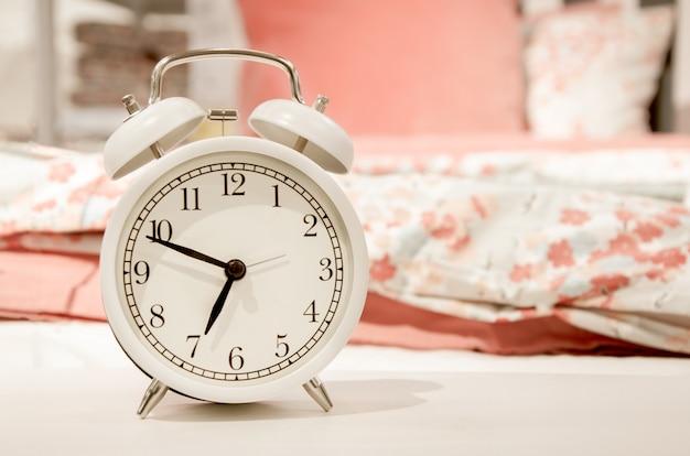 Weißer wecker des klassischen entwurfs, der zeit ungefähr sieben am morgen an der wand der rosa pastelltöne der bettwäsche zeigt