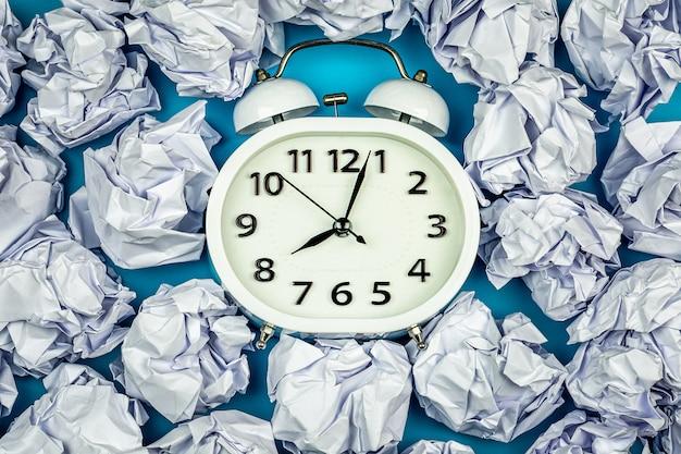 Weißer wecker mit stapel von zerknitterten papierbällen. - denken und timing-ideen-konzept.
