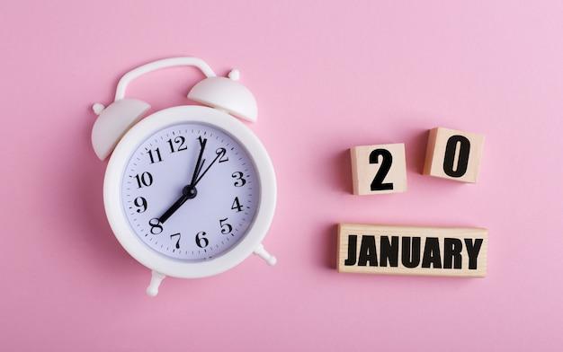 Weißer wecker und holzwürfel mit dem datum 20. januar auf rosa