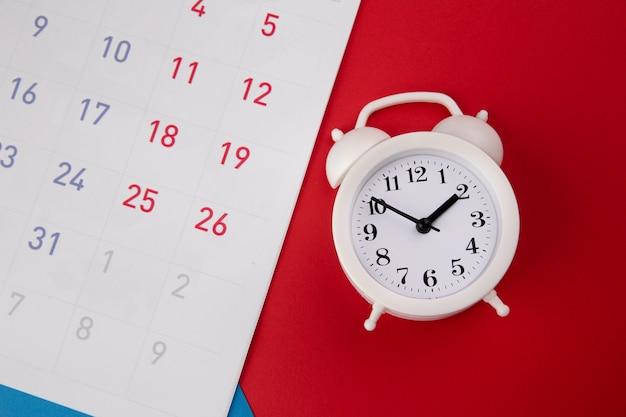 Weißer wecker und kalender auf buntem.