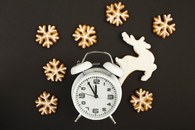 Weißer wecker und weihnachtslebkuchenplätzchen