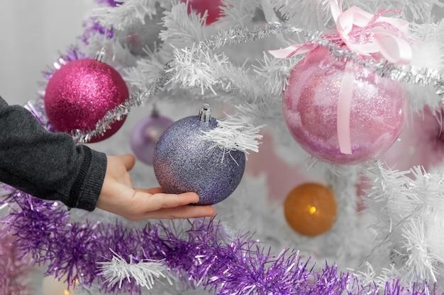 Weißer weihnachtsbaum kinderhand berührt kugeln auf dem weihnachtsbaum nahaufnahme