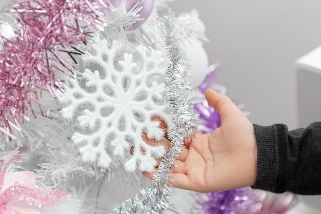 Weißer weihnachtsbaum kinderhand berührt schneeflocke auf dem weihnachtsbaum closeup