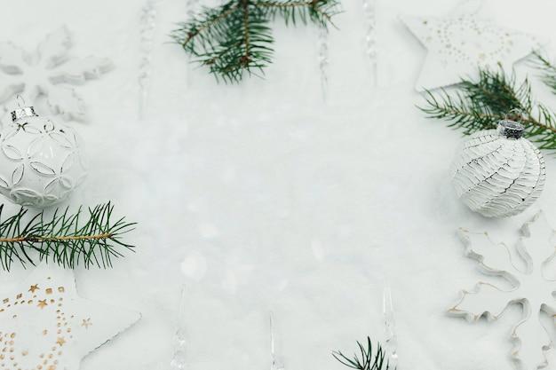 Weißer weihnachtsdekor und tannenzweige auf schnee, weihnachtskarte, weißer weihnachtshintergrund, weiße weihnachtsbälle. foto in hoher qualität