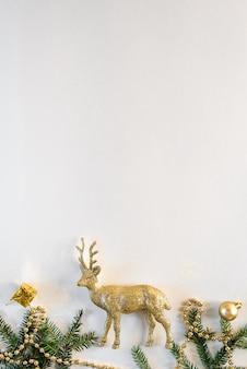 Weißer weihnachtshintergrund mit christbaumspielzeug, goldenen hirschen und tannenzweigen