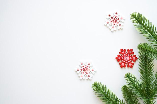 Weißer weihnachtshintergrund mit tannenzweigen und weißen und roten schneeflocken.