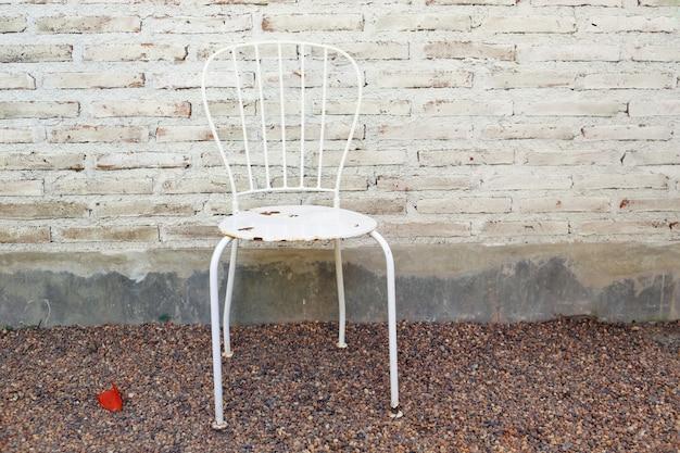 Weißer weinlesestuhl und betonmauer, weichzeichnung und weinleseart.