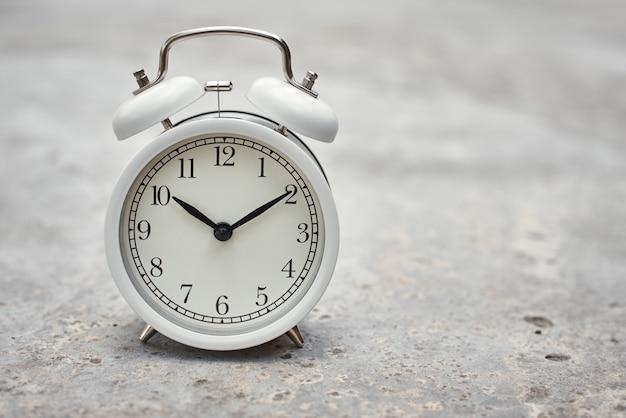 Weißer weinlesewecker auf grauem hintergrund. produktivitätskontrolle und aufgabenplanungskonzept