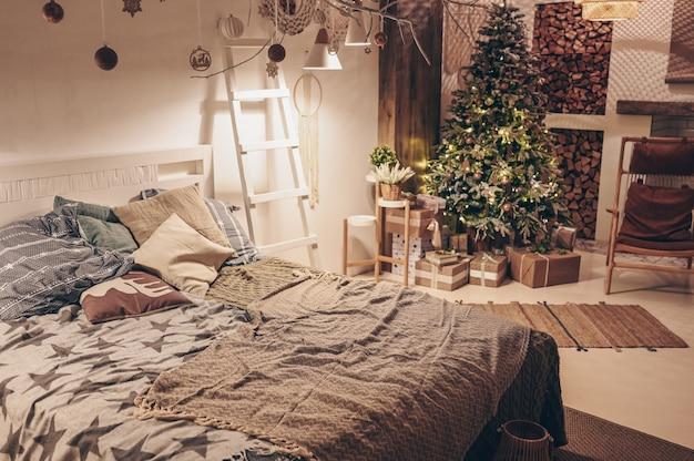 Weißer winter-schlafzimmerinnenraum der skandinavischen art mit verziertem weihnachtsbaum