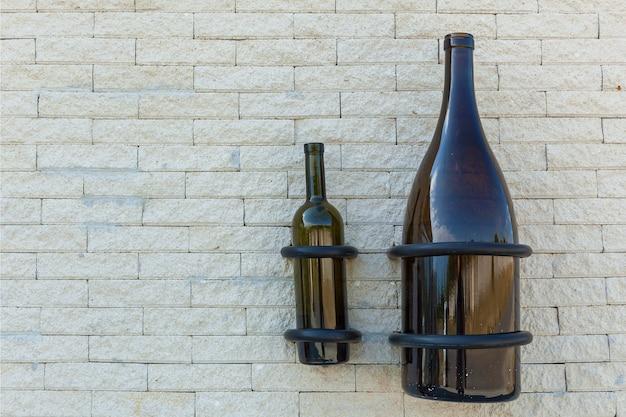 Weißer zaun aus einem stein mit flaschen für wein von einem fass und einem baumschnitt
