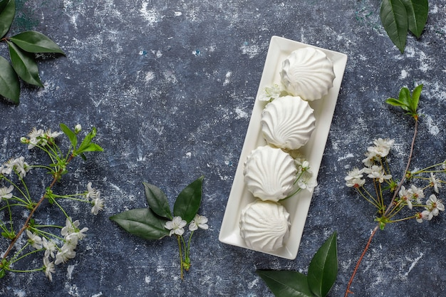 Weißer zephyr, köstliche marshmallows mit frühlingsblütenblüten, draufsicht