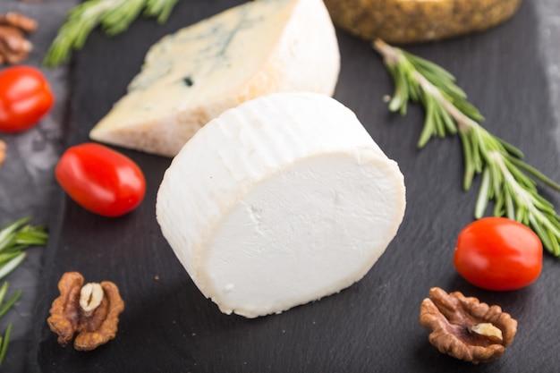 Weißer ziegenkäse und verschiedene käsesorten mit rosmarin und tomaten