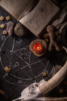 Weißer ziegenschädel mit hörnern, offenes altes buch mit zaubersprüchen, runen, kerzen und kräutern auf hexentisch, flach liegen