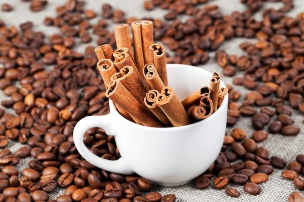 Weißer zimt, gerösteter und duftender kaffee, der in der tasse liegt, nahaufnahme auf dem esstisch