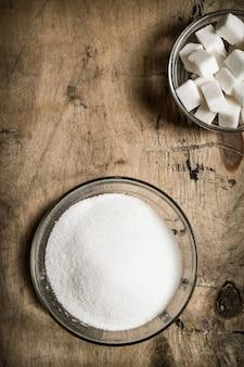 Weißer zucker auf dem hölzernen hintergrund