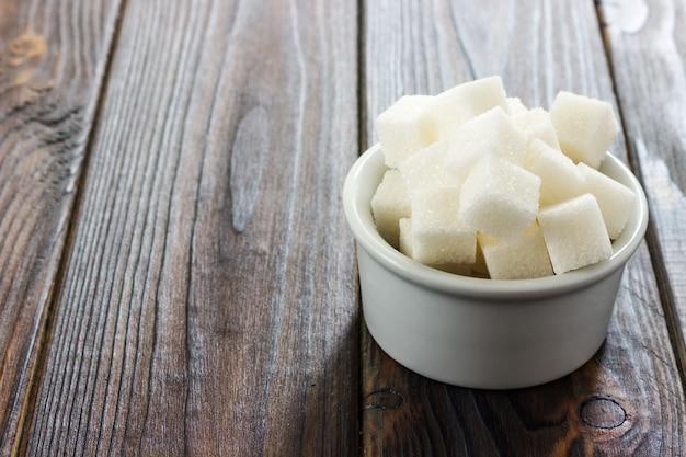 Weißer zucker in der schüssel auf hölzernem hintergrund. selektiver fokus, horizontal. aufnahme von schlechten kalorien