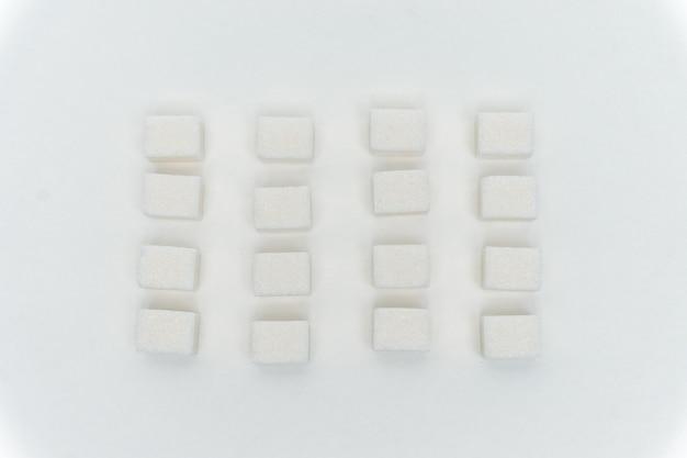Weißer zucker in einer bestimmten reihenfolge auf hellem hintergrund ausgelegt