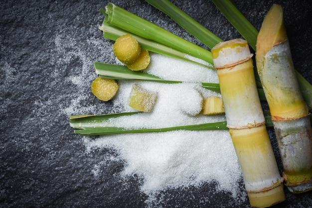 Weißer zucker und und grün des blattes geschnittenes zuckerrohrstück