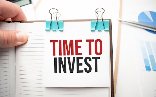 Weißer zukunftsrechner, papierblatt, rosa büroklammern und silberfarbener stift. zeit zu investieren