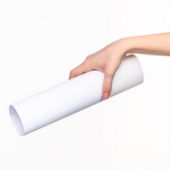 Weißer zylinder der requisiten in den weiblichen händen auf weiß mit rechtem schatten