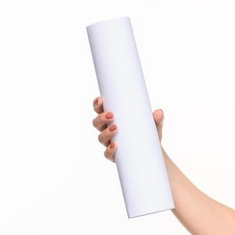 Weißer zylinder der requisiten in den weiblichen händen auf weißem hintergrund mit rechtem schatten