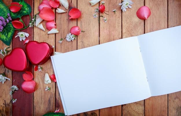 Weißes anmerkungsbuch und roter herzkasten mit den blumenblumenblättern dekorativ auf holztisch. hintergrund für vale