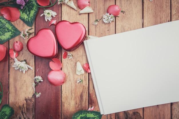 Weißes anmerkungsbuch und roter herzkasten mit den blumenblumenblättern dekorativ auf holztisch.