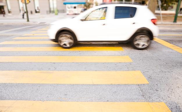 Weißes auto auf dem fußgängerüberweg