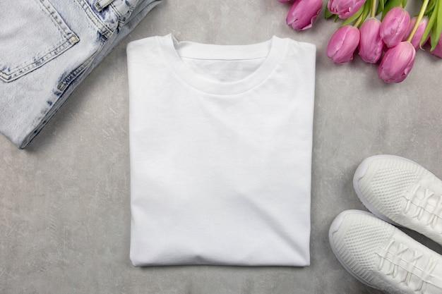 Weißes baumwoll-baumwoll-t-shirt-modell mit rosa tulpen, jeans und turnschuhen. design-t-shirt-vorlage, druckpräsentationsmodell.