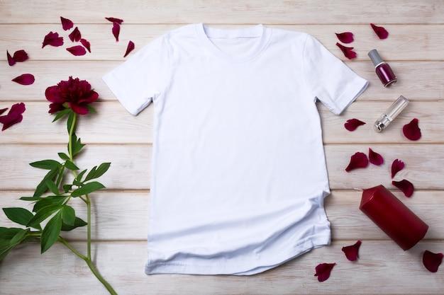 Weißes baumwoll-baumwoll-t-shirt-modell mit roter kerze und burgunderfarbener pfingstrose. design-t-shirt-vorlage, t-shirt-druck-präsentationsmodell
