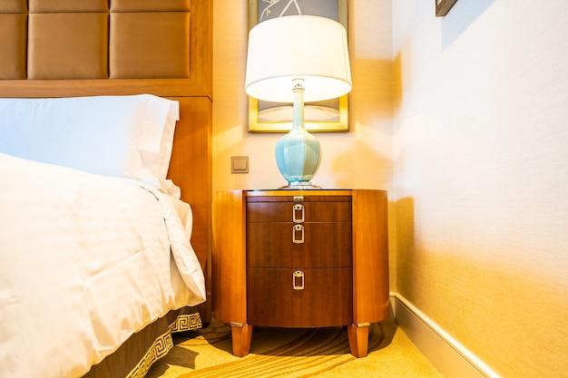 Weißes bequemes kissen auf bett mit tischlicht-lampendekoration im hotelschlafzimmer