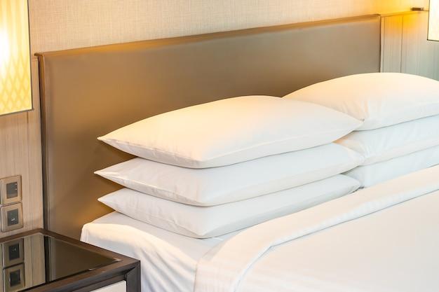 Weißes bequemes kissen und deckendekoration auf bettinnenraum des schlafzimmers