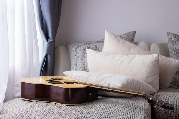 Weißes bett mit gitarre im wohnzimmer, niemand.