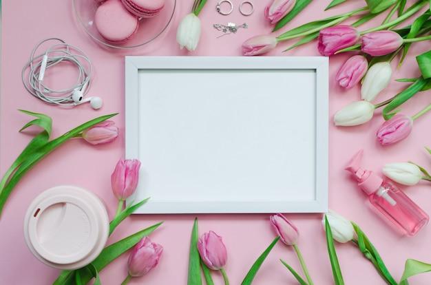 Weißes bild mit kaffeetasse, frühlingstulpenblumen und rosa macarons auf pastelltisch-draufsichthintergrund