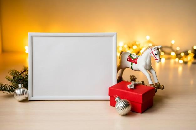 Weißes bilderrahmenmodell des porträts auf tisch mit boken lichtern und weihnachtsdekoration. foto in hoher qualität