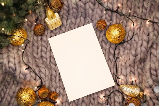 Weißes blatt auf einem gestrickten hintergrund unter weihnachtsdekorationen, flache lage