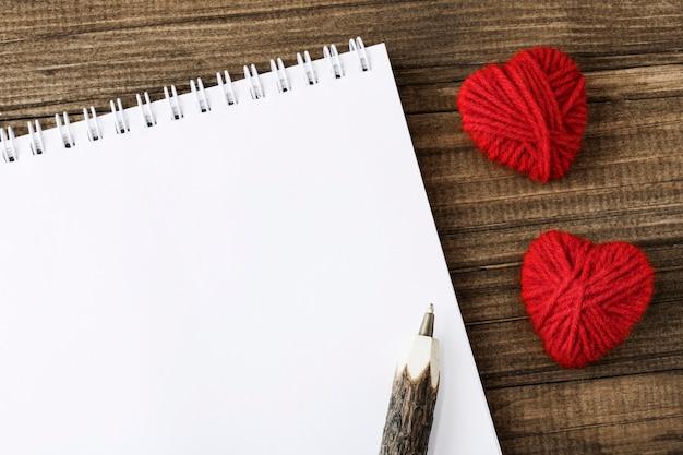 Weißes blatt des notizbuchs neben kreativen roten handgemachten herzen