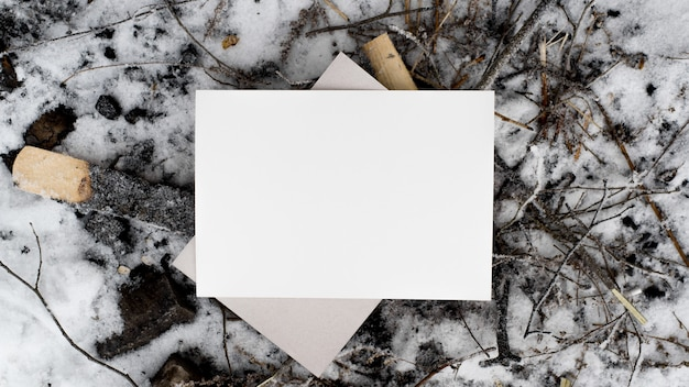 Weißes blatt modell. blatt papier und schwarze kohlen mit schnee, draufsicht. leerer platz für text, flach liegen. postkarte, branding