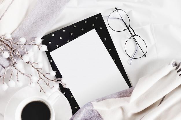 Weißes blatt papier auf dem bett, gläser, ein schal, eine tasse kaffee auf einem weiß. winter flach legen, copyspace,