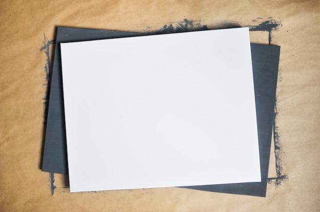 Weißes blatt papier auf dem hintergrund des kraft- und schwarz gestrichenen blattes