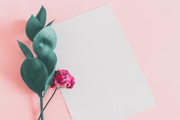 Weißes blatt papier auf einem rosa mit grünen blättern und einer trockenen rosarose
