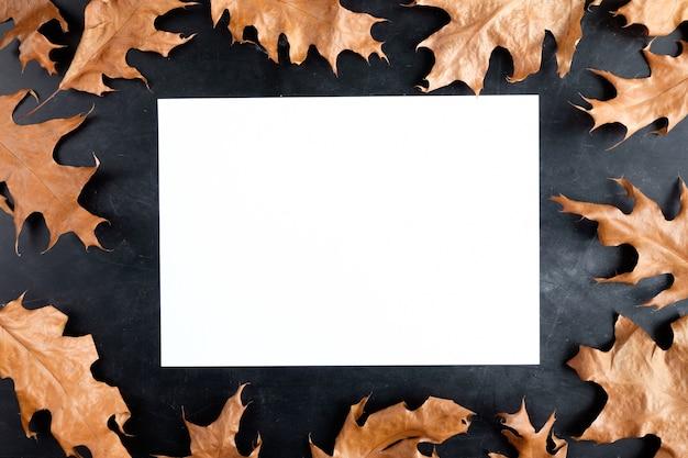 Weißes blatt papier auf schwarzer oberfläche mit gelben blättern