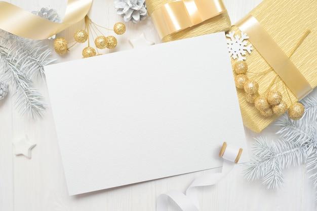 Weißes blatt papier, das unter kleinen dekorationen auf weißem hölzernem schreibtisch liegt.