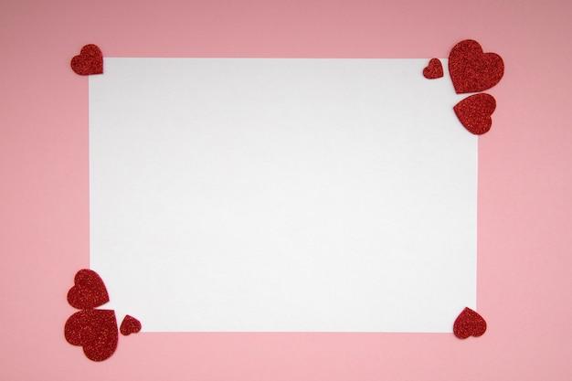Weißes blatt papier für nachricht an einen geliebten menschen auf einem rosa hintergrund mit glänzenden herzen