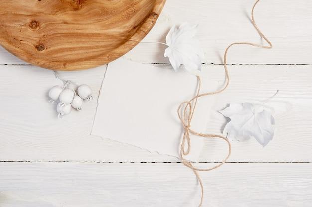 Weißes blatt papier, leinenseil, hölzerner platz, weißer kürbis, beeren und blätter