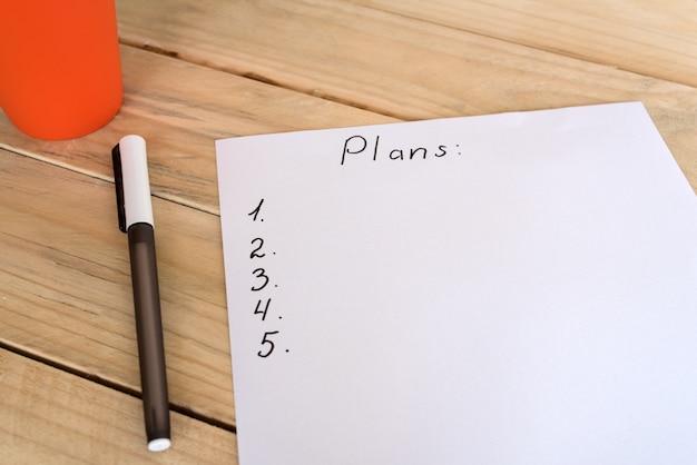 Weißes blatt papier mit schriftlichem plan und punkten. stift, holztisch. geschäftliche planung