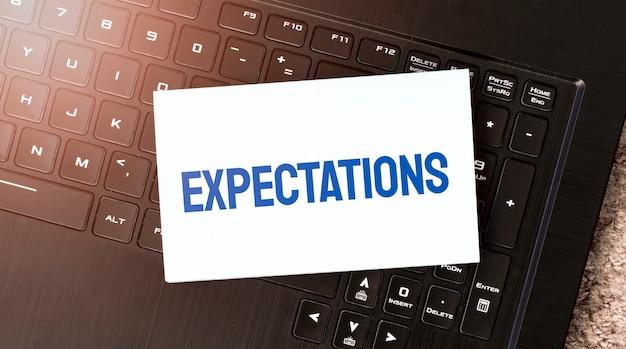 Weißes blatt papier mit text erwartungen auf dem schwarzen laptop