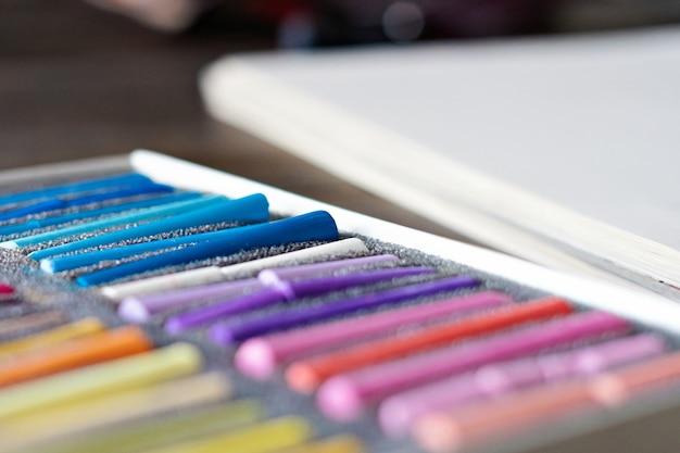 Weißes blatt papier und palette von pastellkreidekreiden