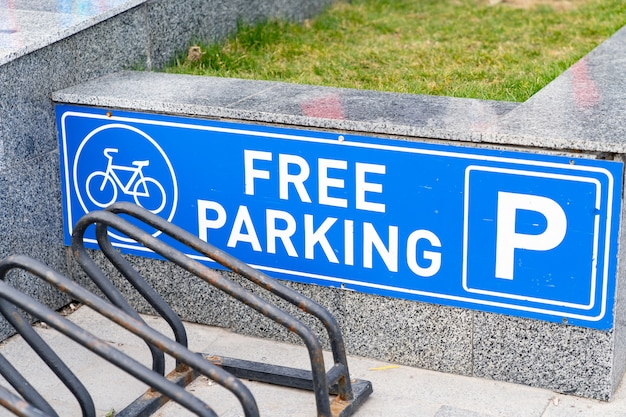 Weißes blaues fahrradparkplatz-straßenschild und freie haltestellen.