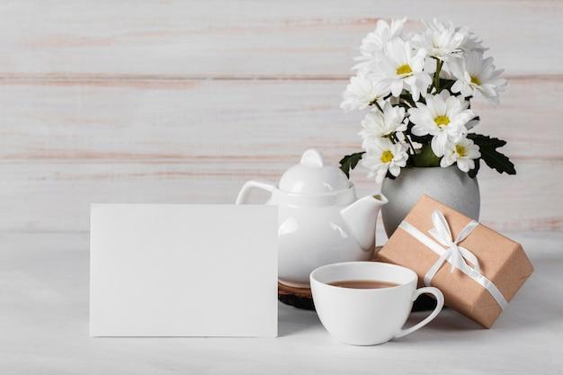 Weißes blumensortiment mit leerer karte und tee